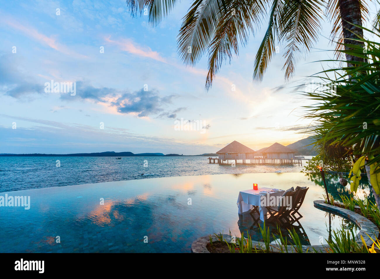 Romantic luxury dinner setting at tropical resort on sunset - Stock Image