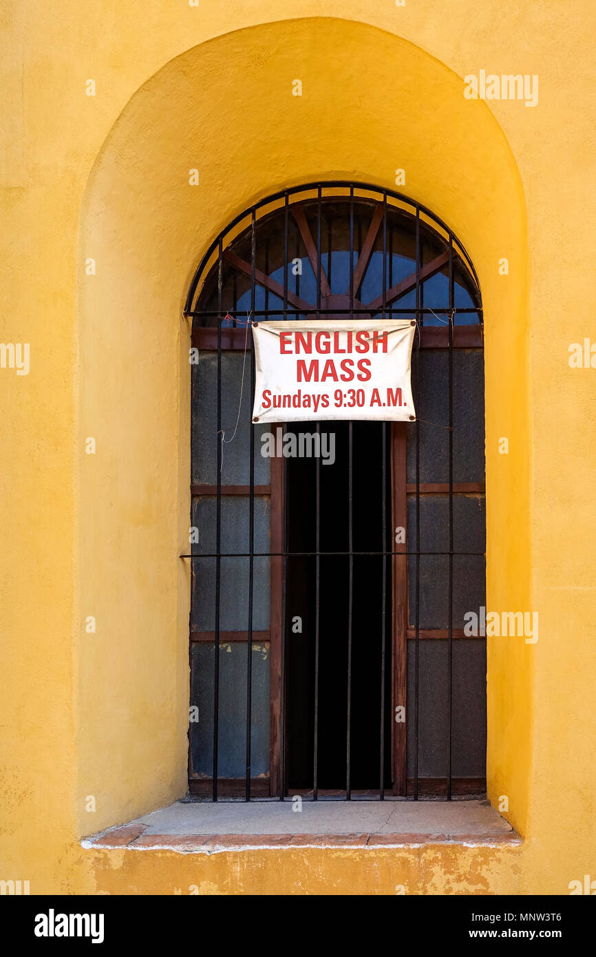 A sign in the window of a Catholic Church in San Miguel de Allende, Mexico announcing a mass in English - Stock Image