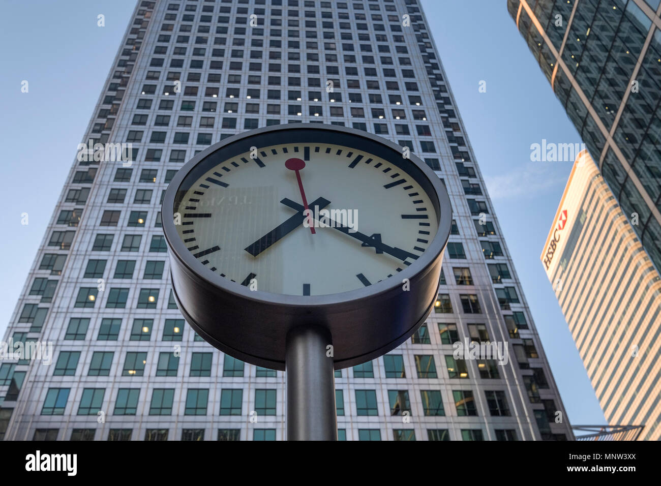 Canary Wharf Clock backed by 1 Canada Square Building, Reuters Plaza, Canary Wharf, London, England, UK - Stock Image