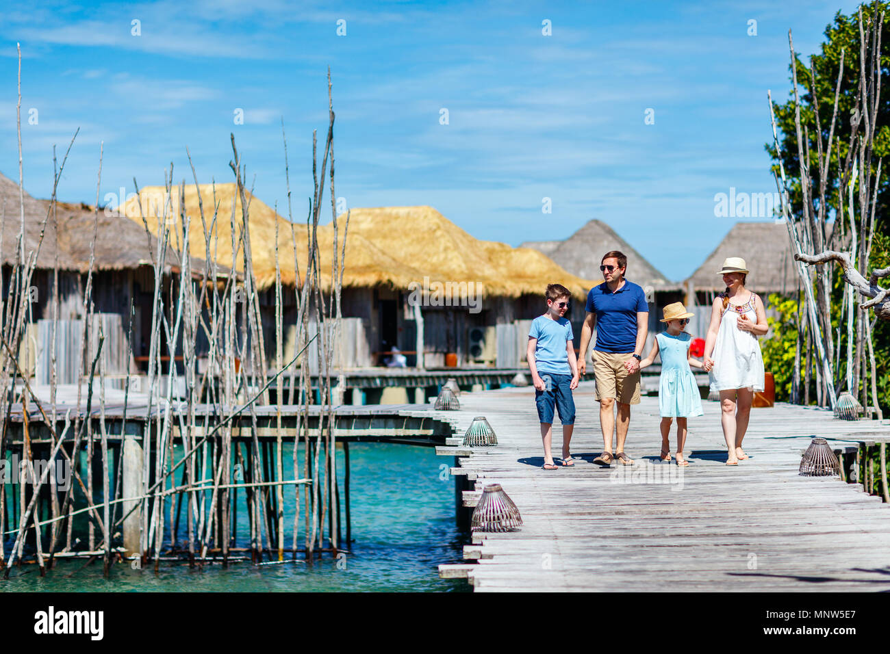 Happy beautiful family walking on wooden jetty during summer vacation at luxury resort - Stock Image