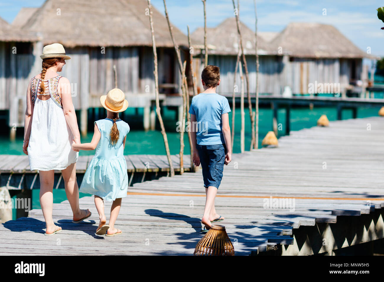 Back view of happy beautiful family walking on wooden jetty during summer vacation at luxury resort - Stock Image