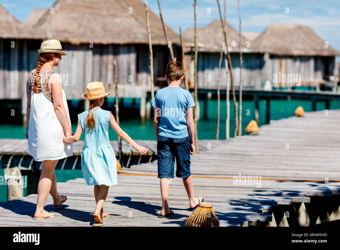 Back view of happy beautiful family walking on wooden jetty during summer vacation at luxury resort Stock Photo