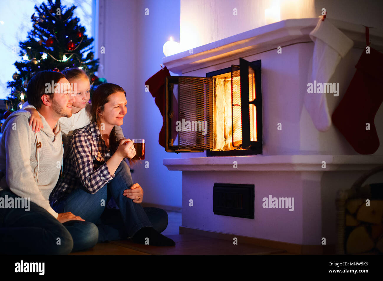 Family sitting by a fireplace in their family home on Christmas eve - Stock Image