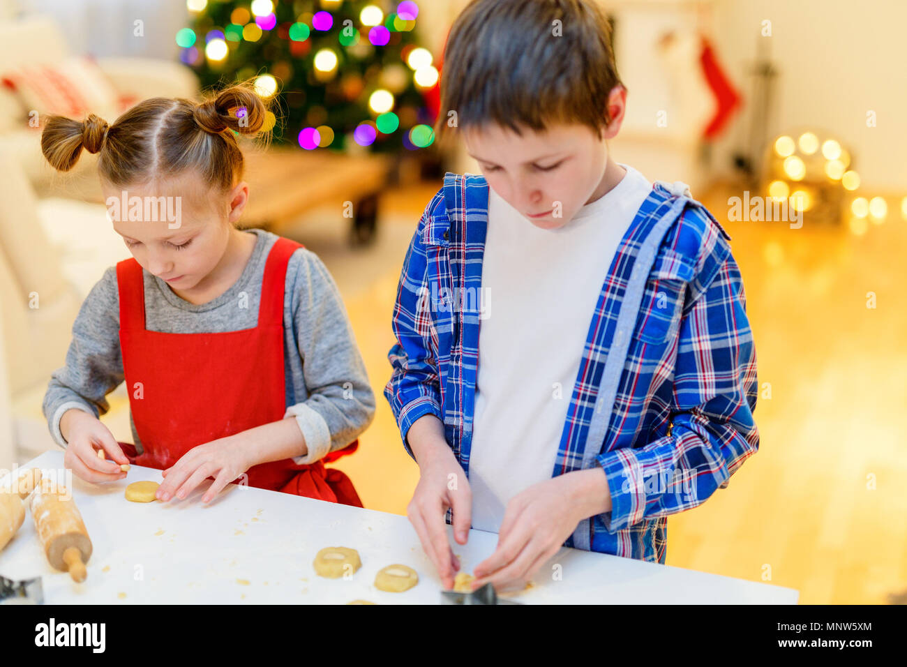 Two kids baking gingerbread cookies at home on Christmas eve - Stock Image