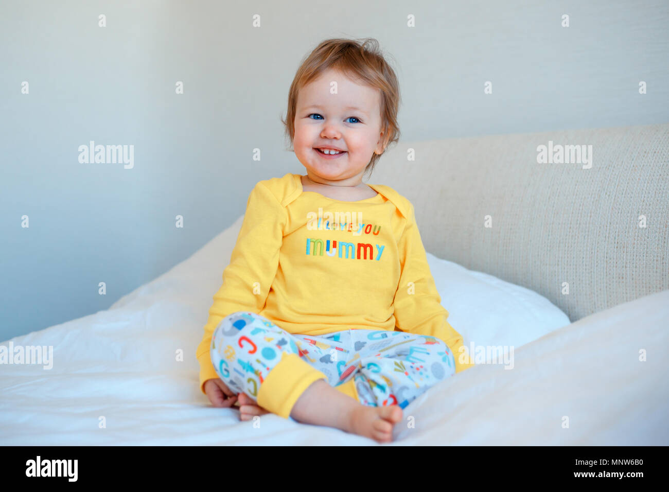 5c5ad04e7021 Funny little baby girl sitting in parents bed. Infant girl in yellow ...