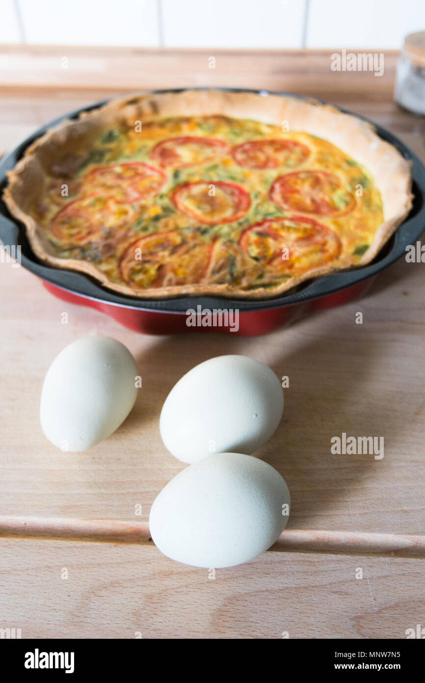 fresh quiche with green eggs, tomatos and spring onions Stock Photo