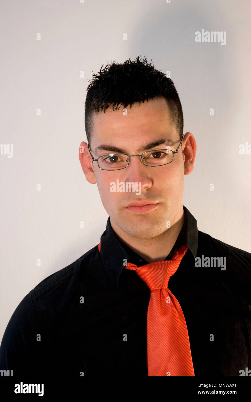 748131b04a00 Young man wearing black shirt, red tie and spectacles, looking at the  camera.