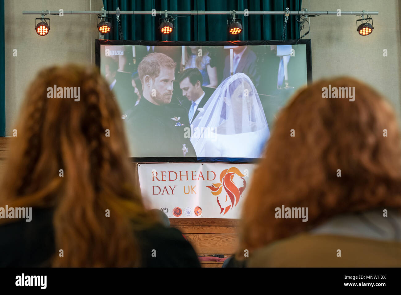 London, UK. 19th May 2018. Prince Harry is watched by redheads during the live broadcast of the royal wedding at Redhead Day UK in north London. The annual event sees hundreds of 'gingers' from around the world join in celebration of red hair. Credit: Guy Corbishley/Alamy Live News - Stock Image
