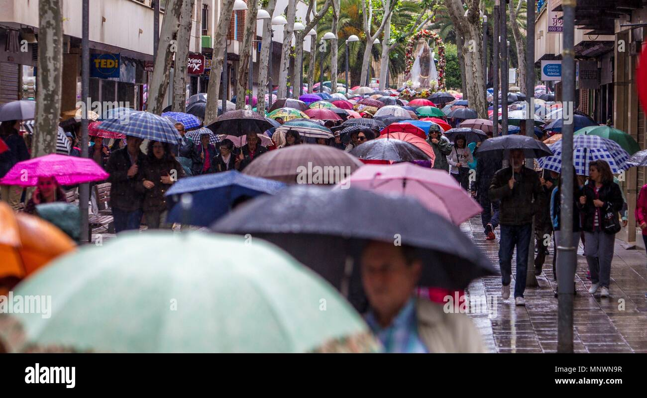 Ciudad Real, Spain. 20th May, 2018. Visitors protect themselves from the rain with umbrellas as the traditional pilgrimage of the Virgin of Alarcos is canceled in Ciudad Real, Spain, 20 May 2018. The pilgrimage and the procession were finally suspended due to the rain. Credit: Mariano Cieza/EFE/Alamy Live News - Stock Image
