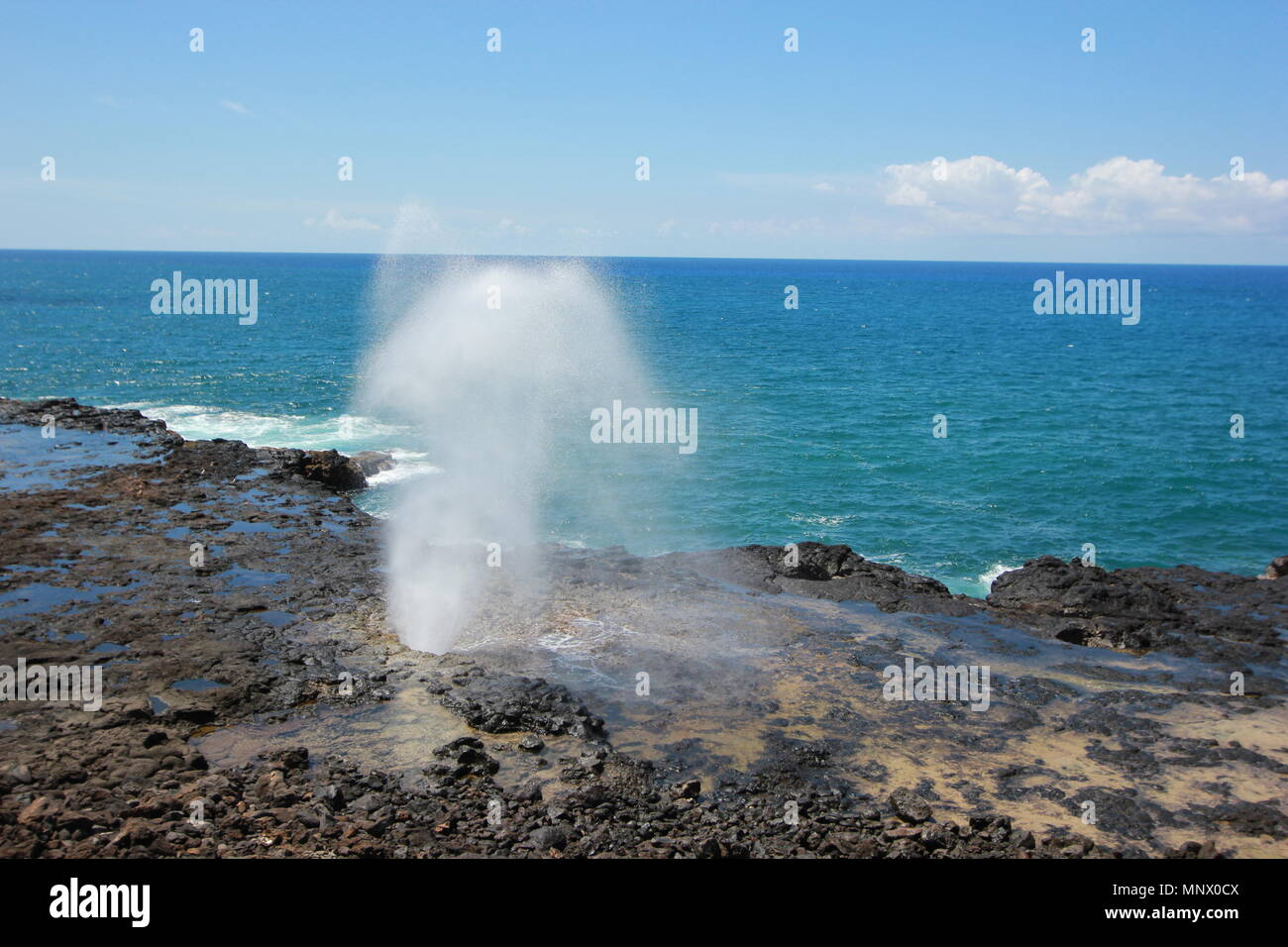 Spouting Horn is off the southern coast of Kauai in the Koloa district and is known for its crashing waves and large spray of water. - Stock Image