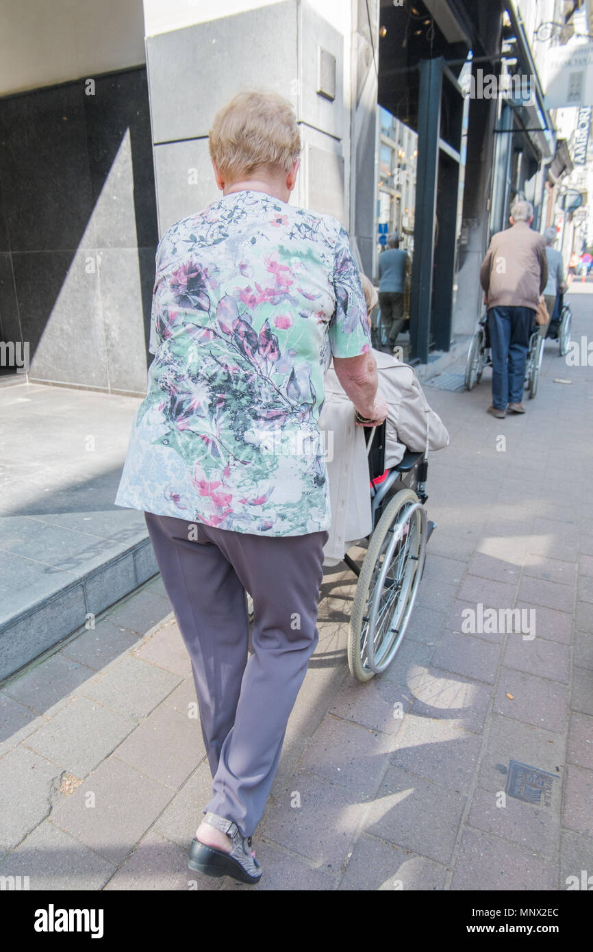 Old women pushing another women in a wheel chair, antwerp, belgium Stock Photo