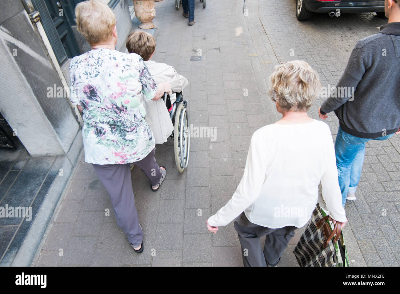 Old women pushing another women in a wheel chair, antwerp, belgium Stock Photo