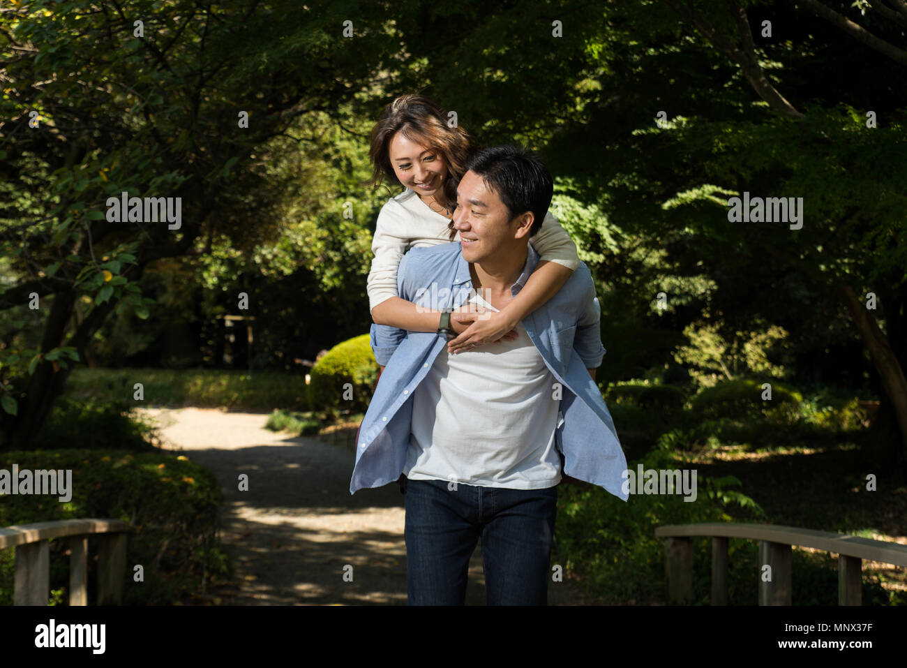 Beautiful asian couple dating in a park - Japanese man and woman having fun outdoors - Stock Image