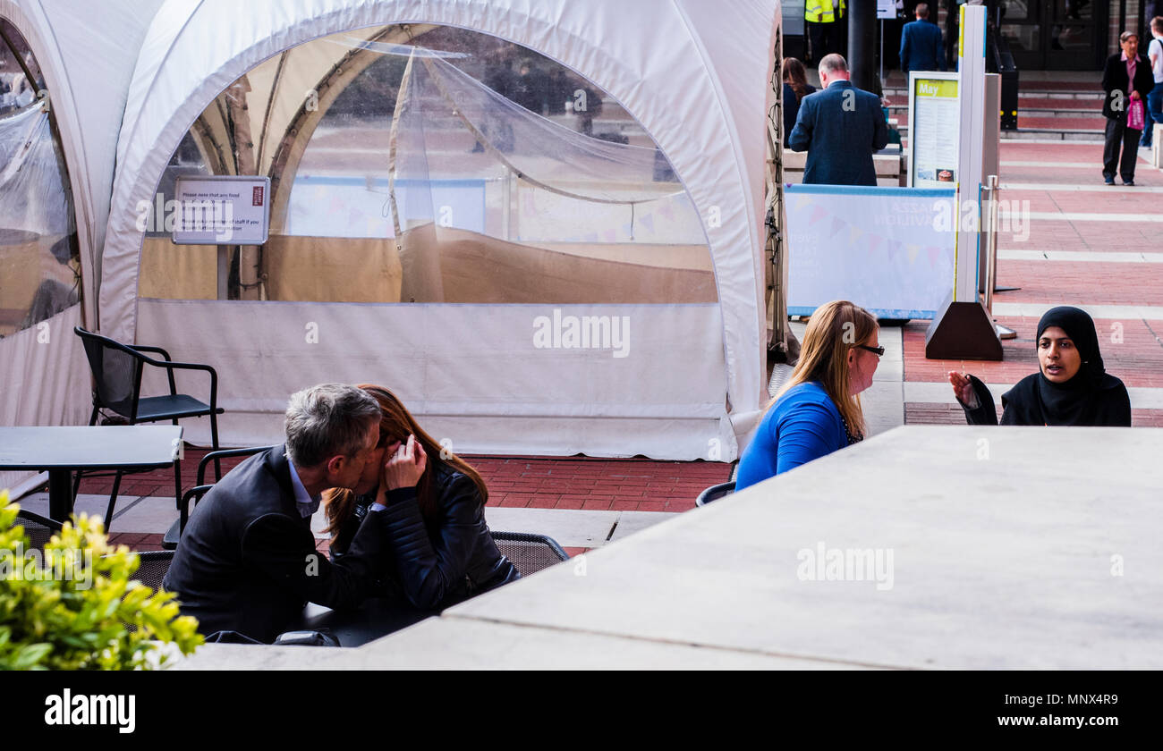 Couple kissing in the outside area of the British Library while two women talk in the background. London, England, UK Stock Photo