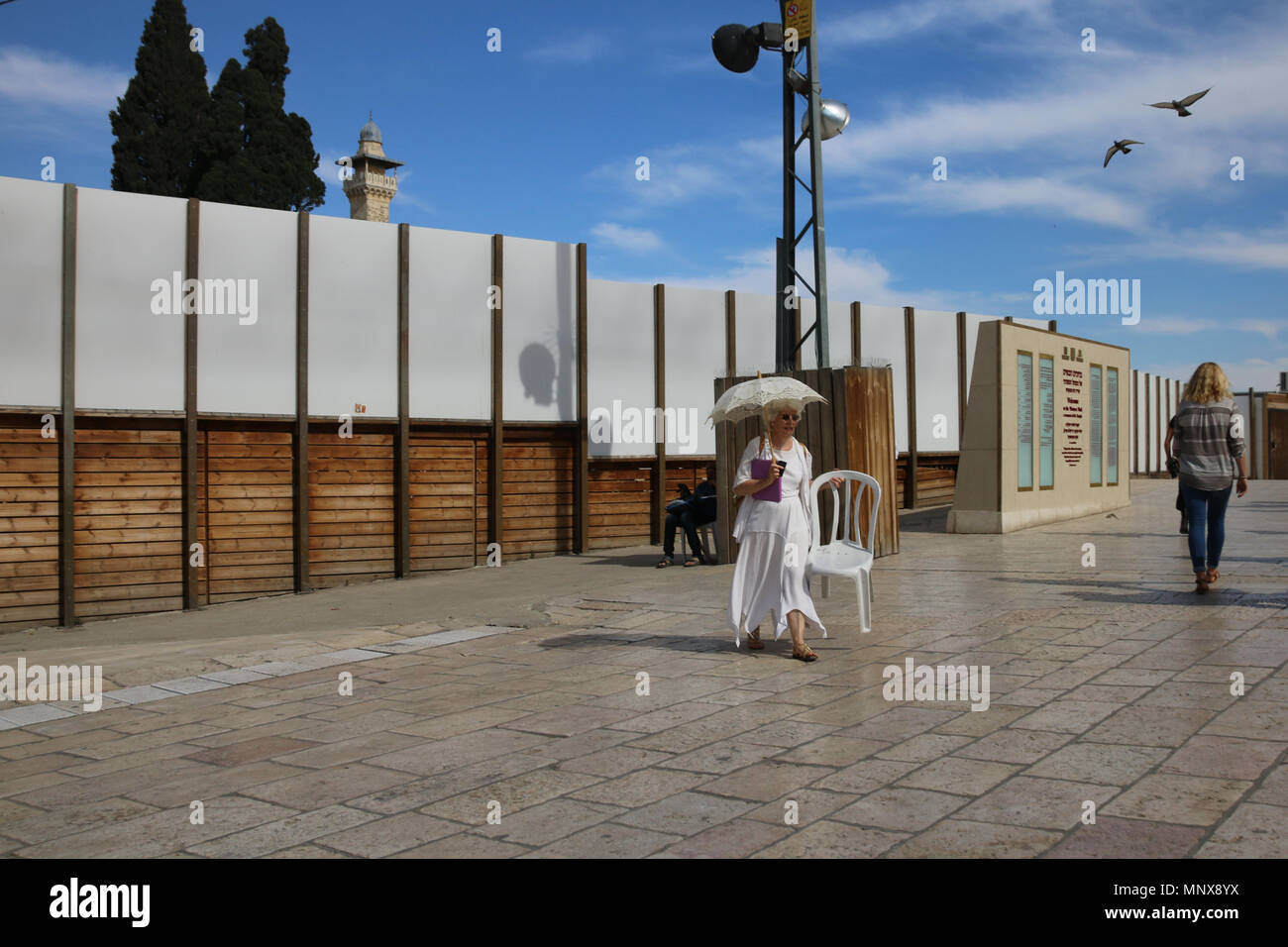Jerusalem, Israel - May 16, 2018: A woman with a white umbrella and white dress wears a white chair across the square in front of the Wailing Wall in  - Stock Image