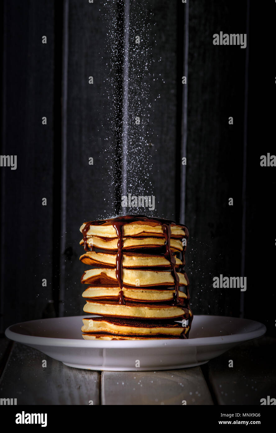 Fresh and delicious sweet pancakes with falling sugar on top, and chocolate syrup sauce - Stock Image