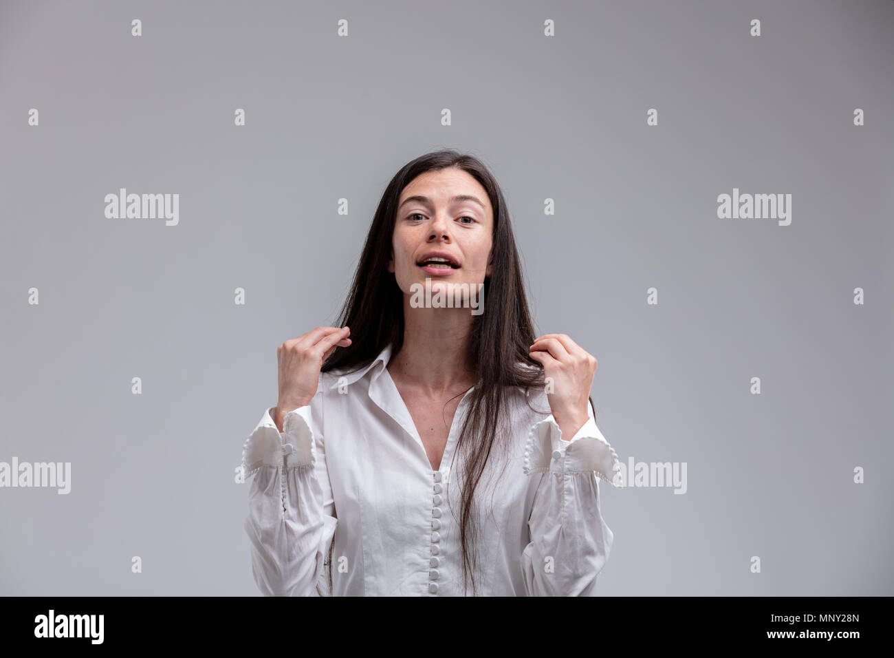 Portrait of young long-haired brunette persuasive woman explaining problem - Stock Image