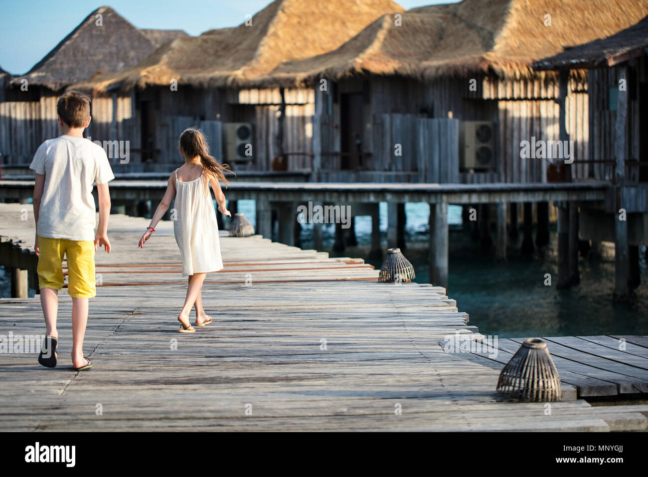 Kids brother and sister walking on wooden footbridge during summer vacation at luxury resort - Stock Image