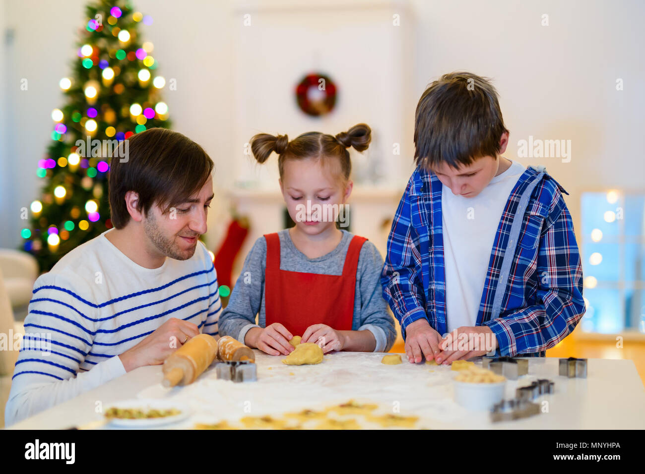 Family of father and kids baking cookies at home on Xmas eve. Beautifully decorated room, Christmas tree and lights on background. - Stock Image