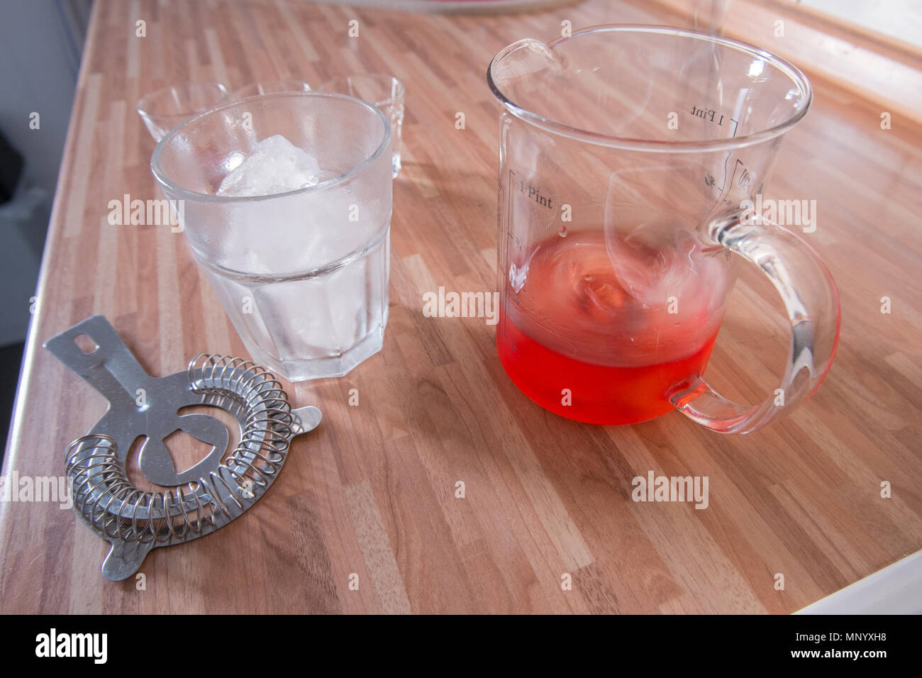Mixing a negroni cocktail on wooden kitchen worktop Stock Photo
