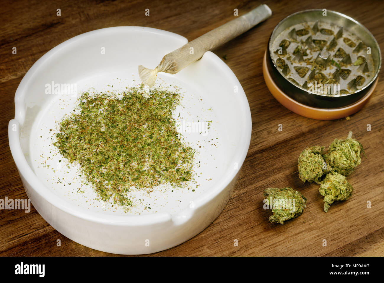 Crumbled weed in the shape of Suriname and a joint. (series) - Stock Image