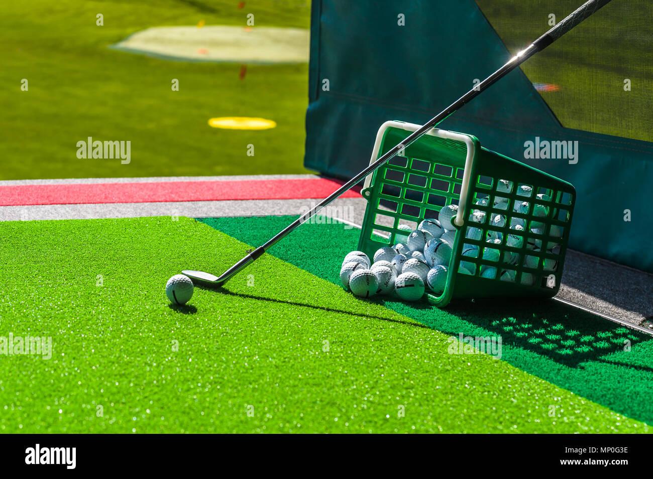 Golf balls, basket of balls & Golf clubs at driving range images - Stock Image