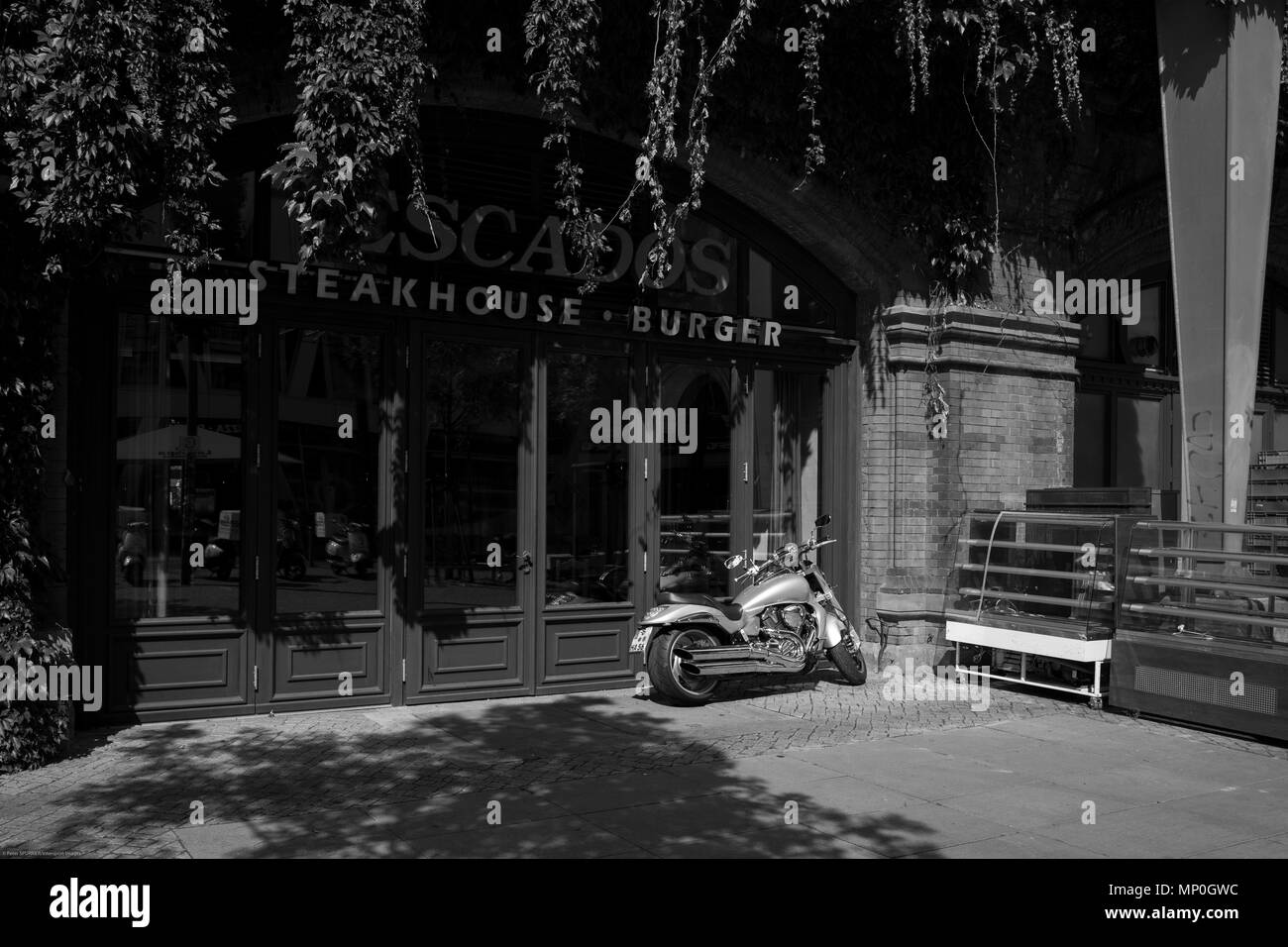 Berlin, Germany.  General View. Hackescher Markt area station. Steak House and Burger Restaurant, Motor Bike, parked, on the forecourt,  Black and White,  Monday  28.08.17.   © Peter SPURRIER, - Stock Image
