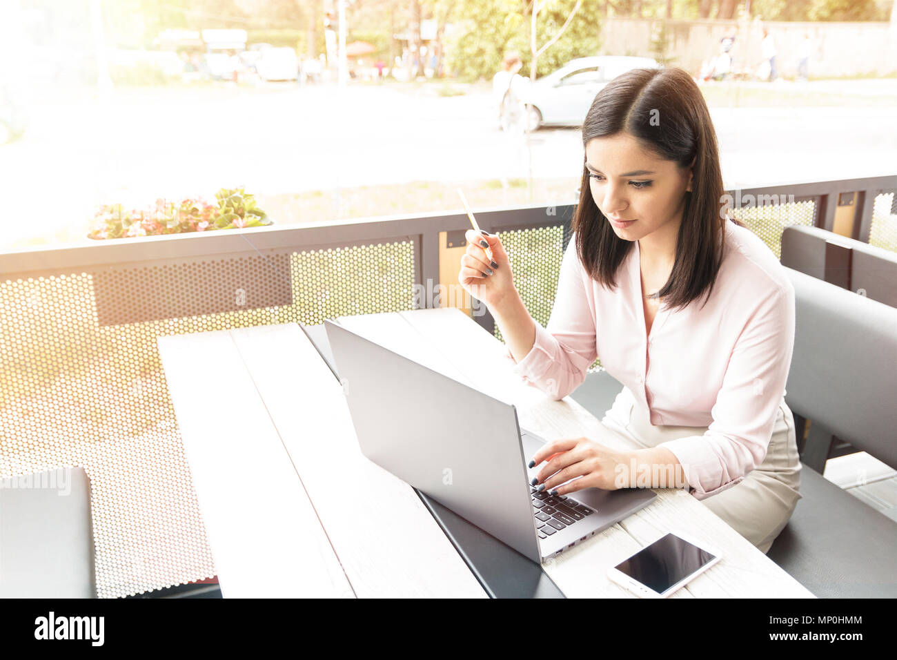 Image of young woman using laptop while sitting at cafe. - Stock Image