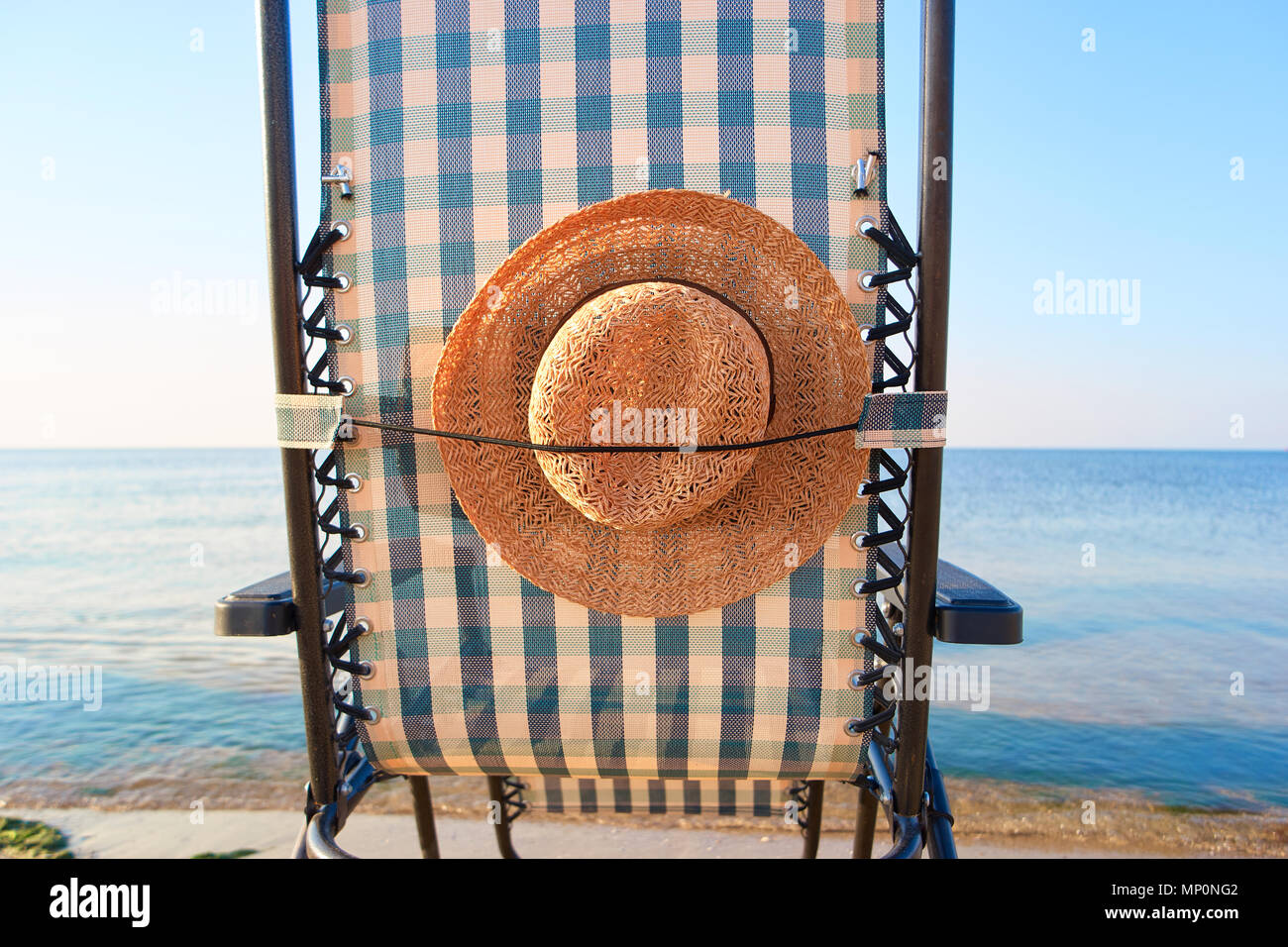 Close up rear view sun hat attached to deck chair. - Stock Image