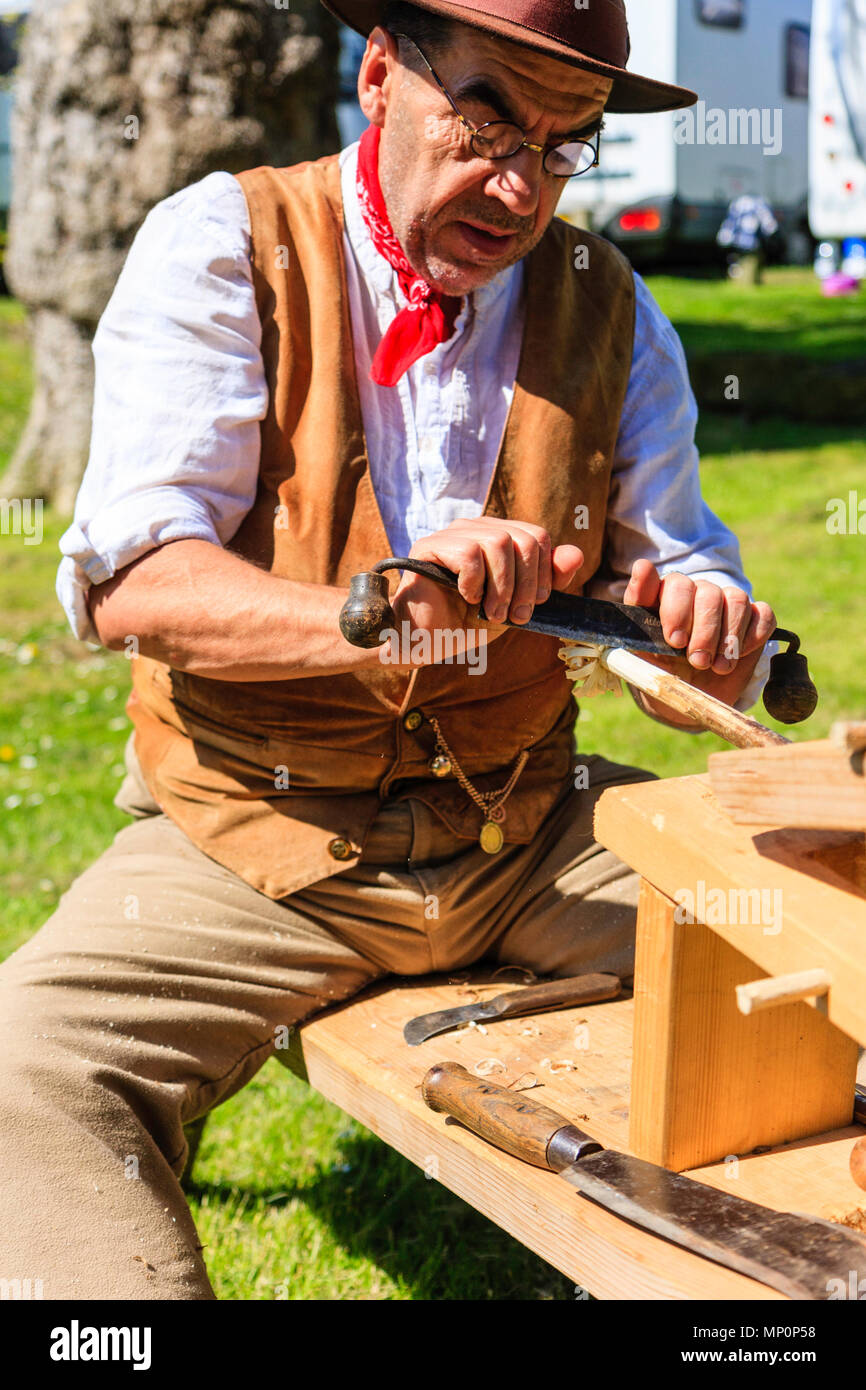 Salute to the 40s popular event. Carpenter, woodworker in 1940's country clothing using a drawknife to shave a wooden pole held on workbench. - Stock Image
