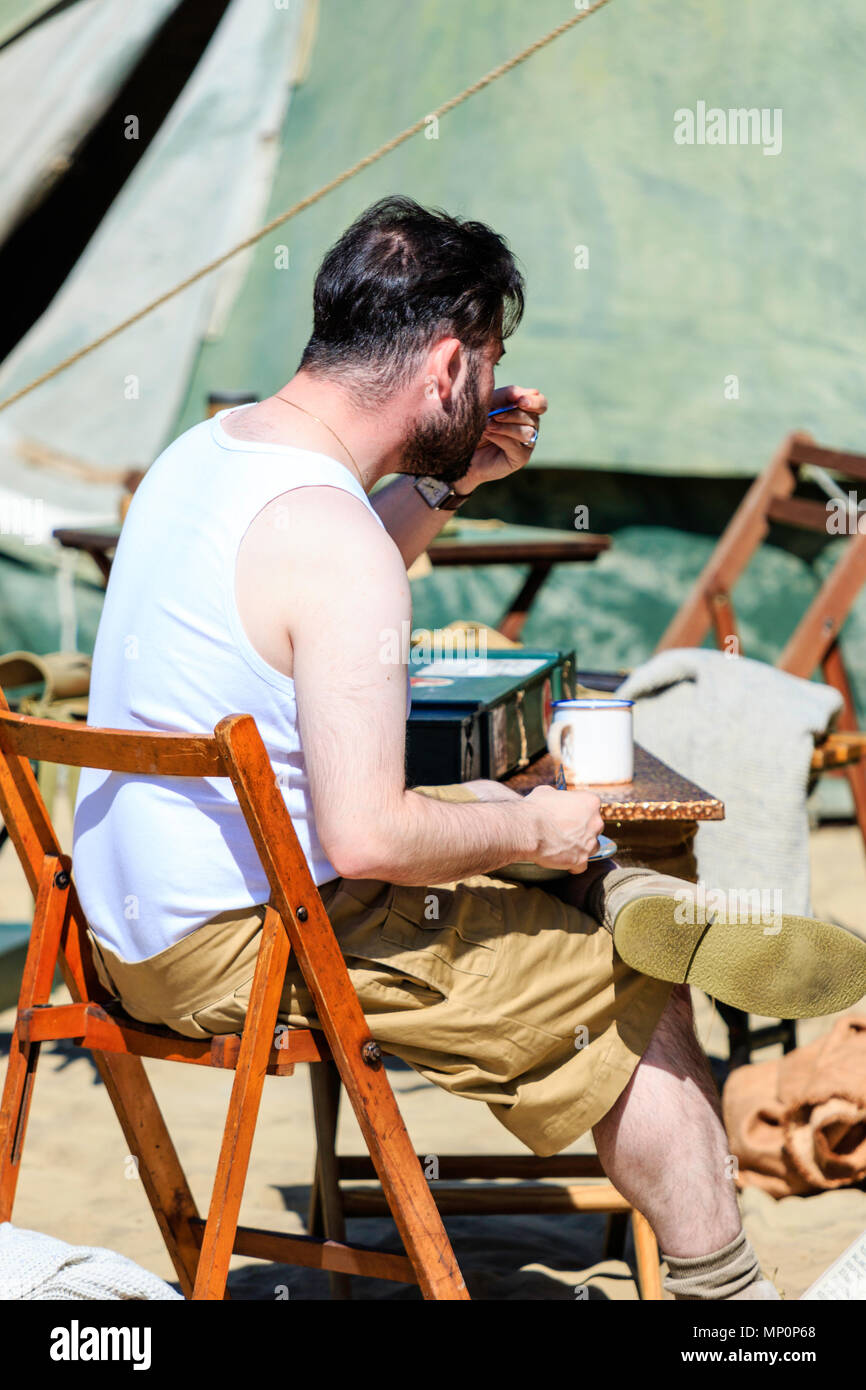 Salute to the 40s popular event in England. Re-enactor sitting in army trousers and white vest eating food from metal tray in Desert Rats encampment. - Stock Image