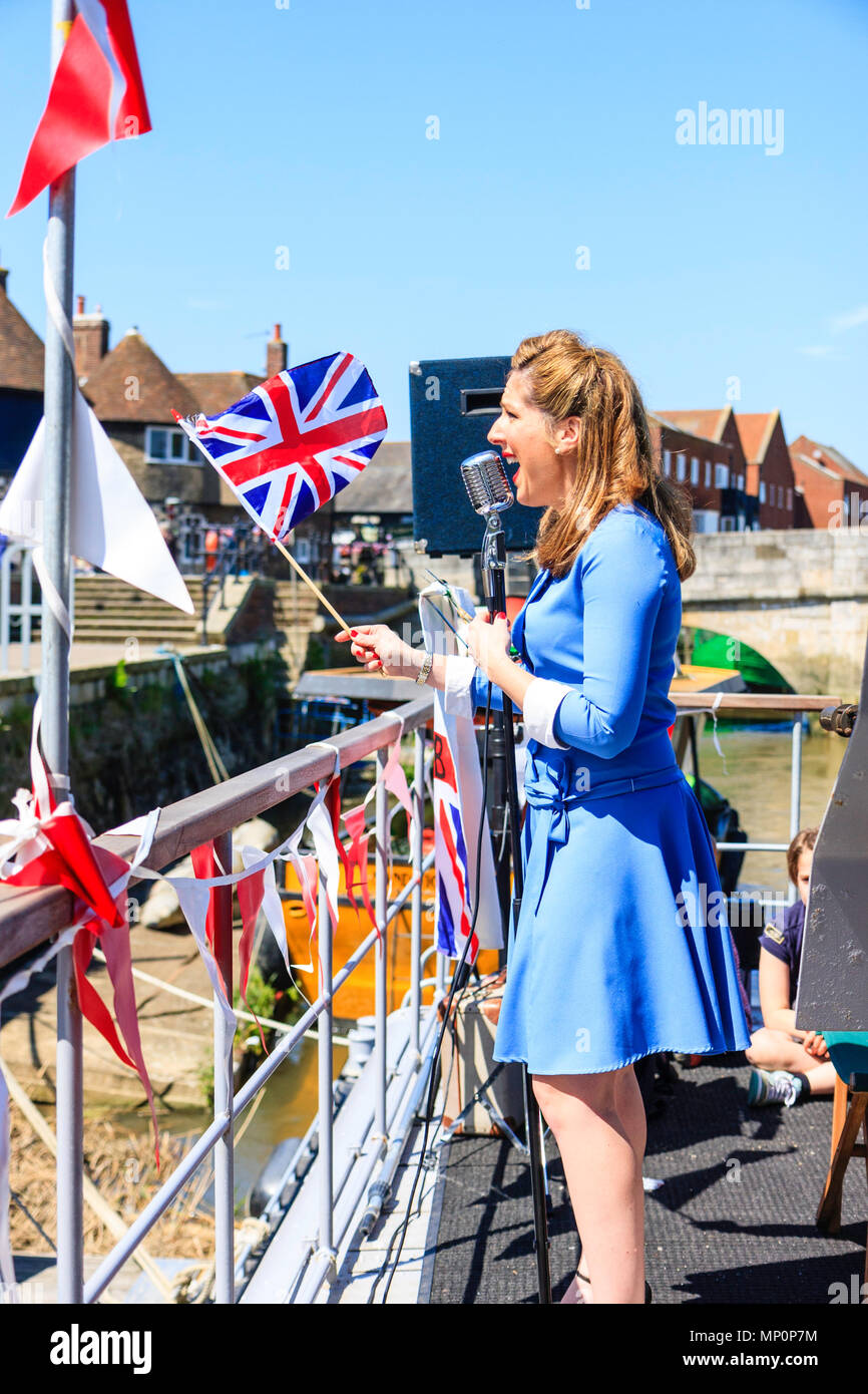Salute to the 40s popular nostalgic. Midadult Woman singer from the Victory Wartime Band, waving Union Jack and singing on deck of P22 at Sandwich. - Stock Image