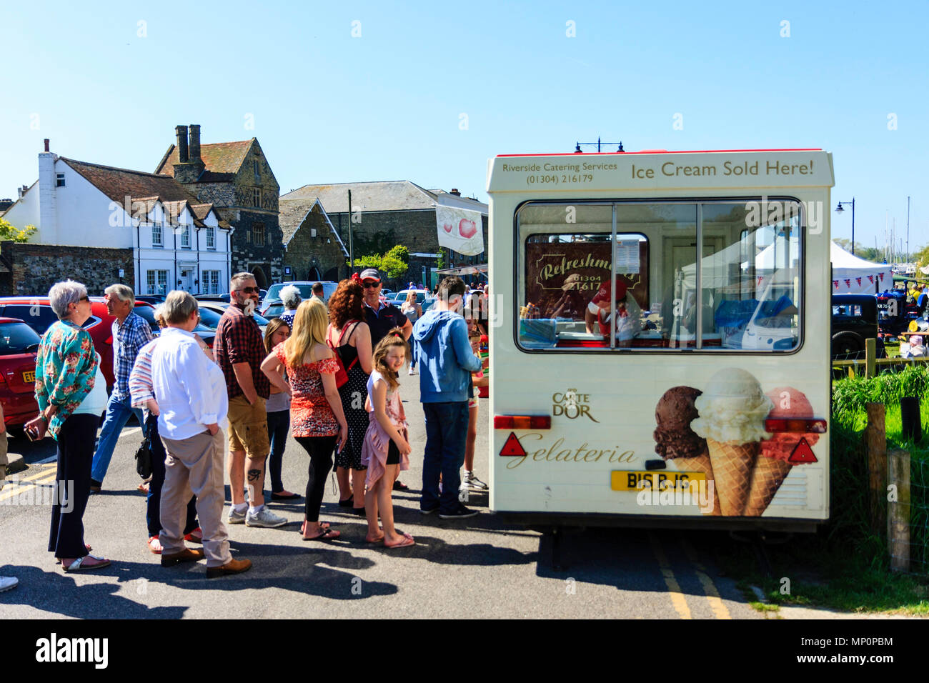 England. People queuing waiting to buy ice creams from ice cream van on a hot day. Sunshine, blue sky. - Stock Image
