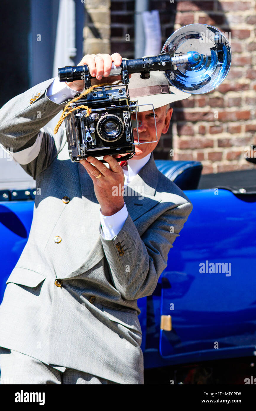 Salute to the 40s event at Sandwich in Kent. Man reenactor dressed as photo journalist with Graflex Speed graphic camera, taking picture of viewer. - Stock Image