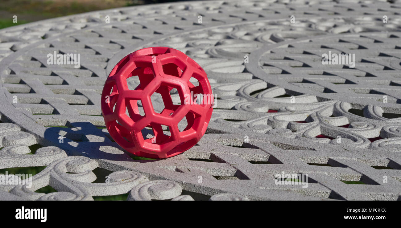 A Red hexagonal Dog Treat Ball sits on a metal Garden Table in a Garden. Arbroath, Angus, Scotland. - Stock Image