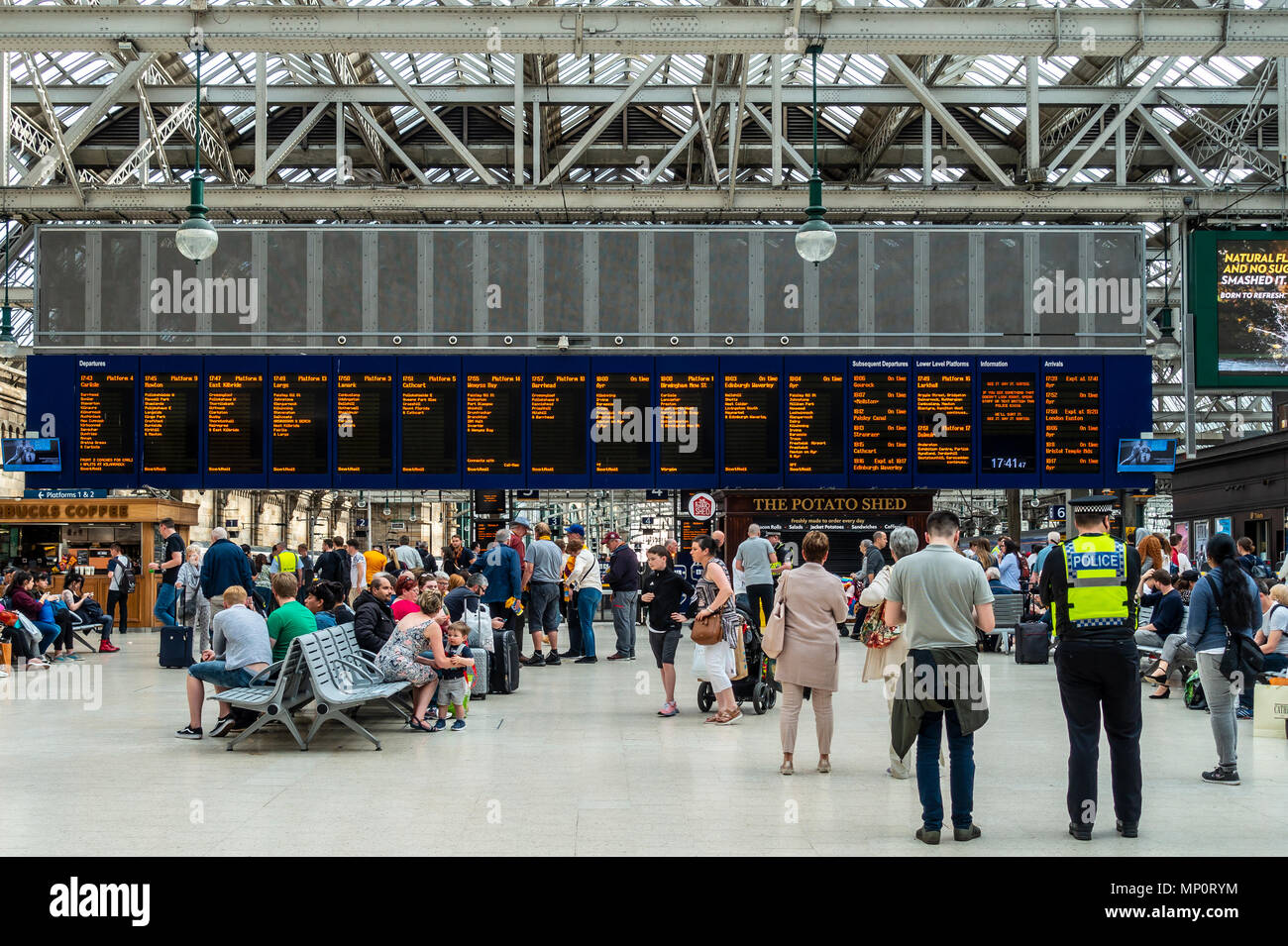 Passengers waiting for trains in front of the main Departures Board in the concourse of Glasgow Central Station, Glasgow, Scotland, UK - Stock Image