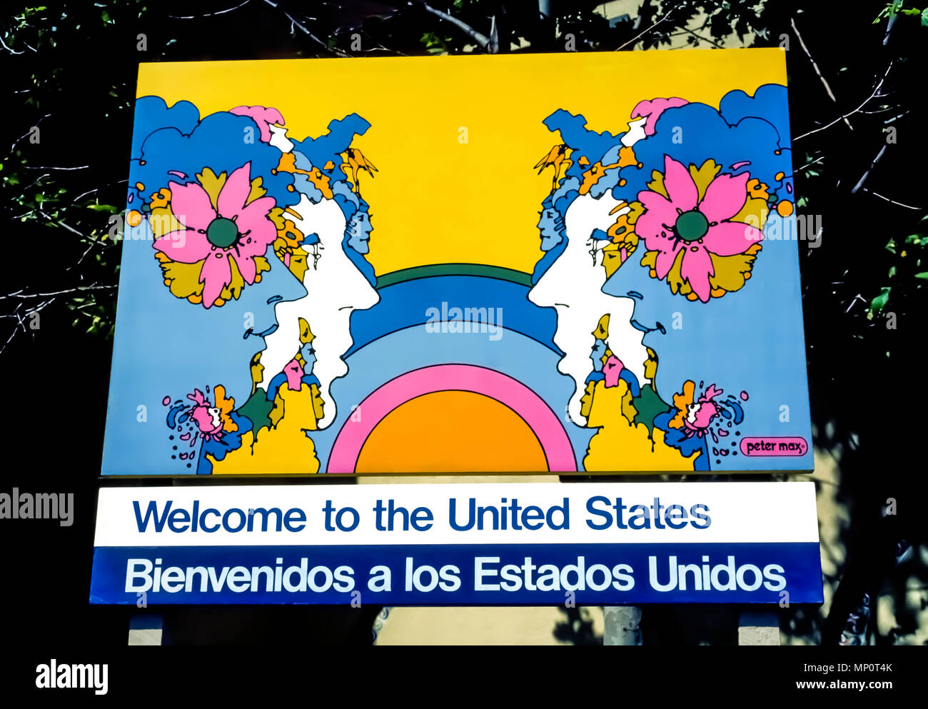 A U.S. government sign illustrated by American artist Peter Max welcomes visitors and immigrants to the United States in English and Spanish languages at the international border crossing at Tijuana, Mexico, in North America. A master of pop art known for using bright colors in his work, Max is the official portrait artist for welcome banners at U.S. ports of entry. - Stock Image