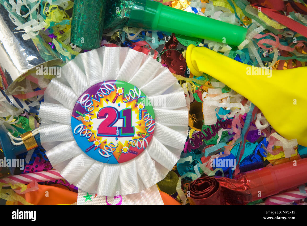 Close Up Shot Of A 21st Birthday Ribbon Rosette Surrounded By Party Decorations