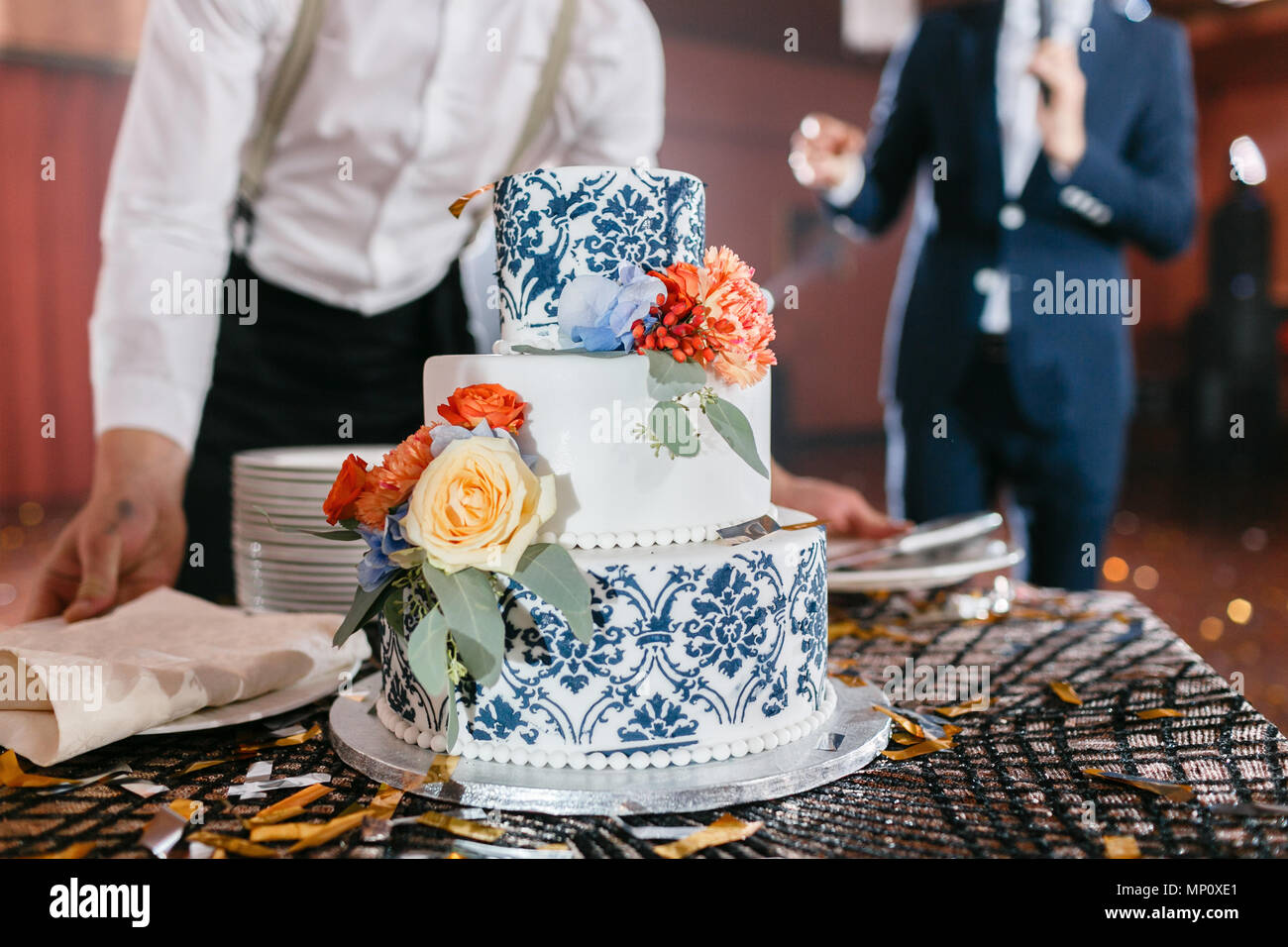 waiter will present at the restaurant. Wedding cake with flowers. Bride and groom cut sweet cake on banquet in restaurant. - Stock Image