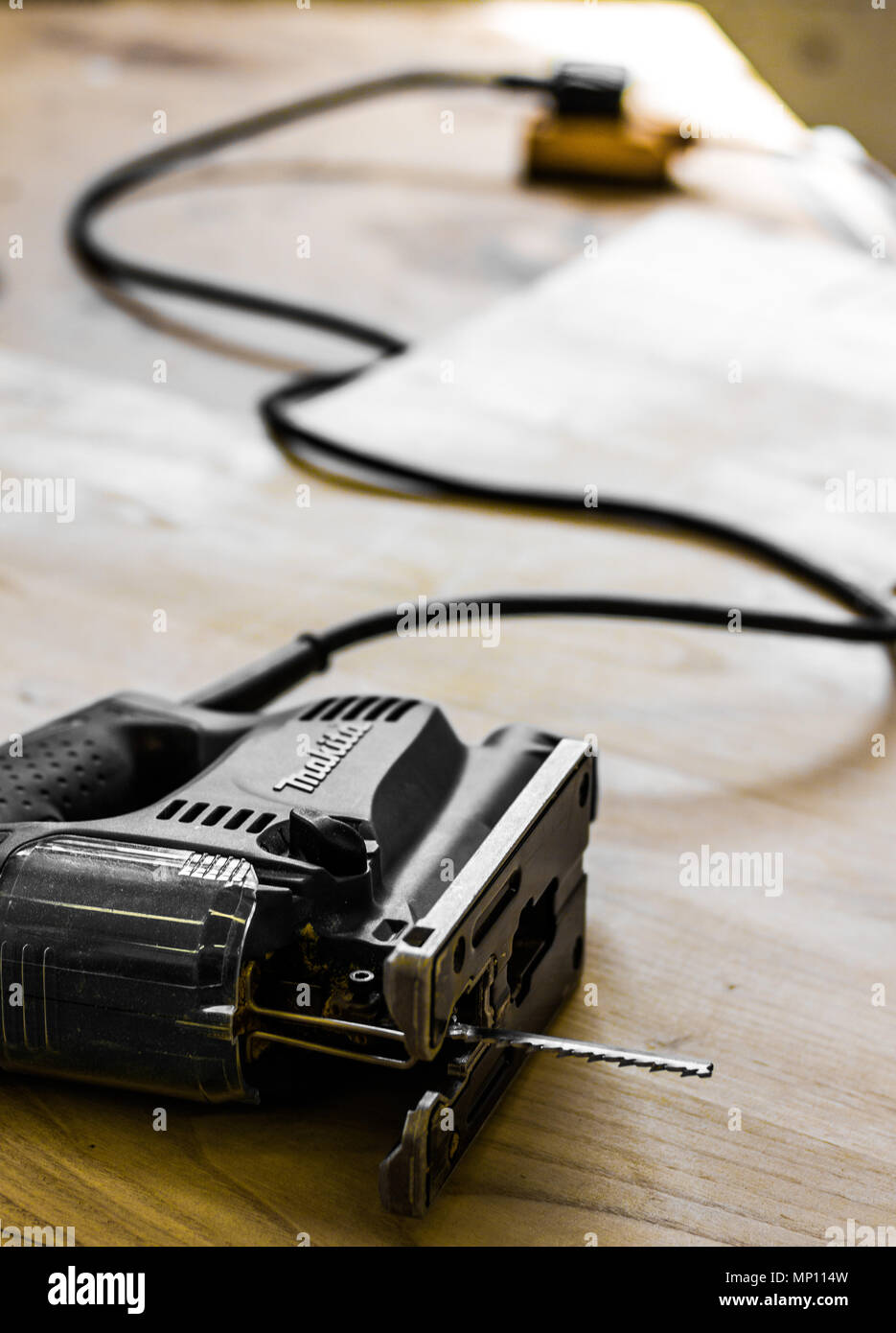 Jigsaw tool close up lying on a work bench plugged in - Stock Image