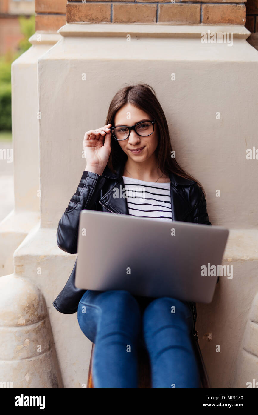 Young female blogger chatting with followers and sending feedbacks resting on bench in town with netbook,hipster girl working on freelance using lapto - Stock Image