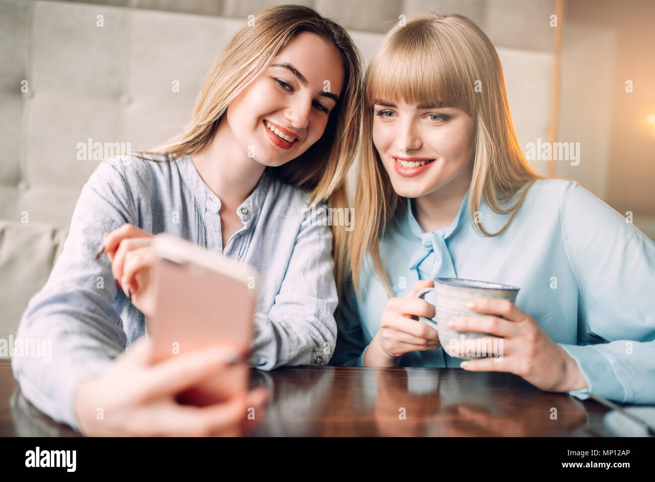 Young woman shows photos on phone to her girlfriend in cafe. Female friends leisures in restaurant, gossipers meeting - Stock Image