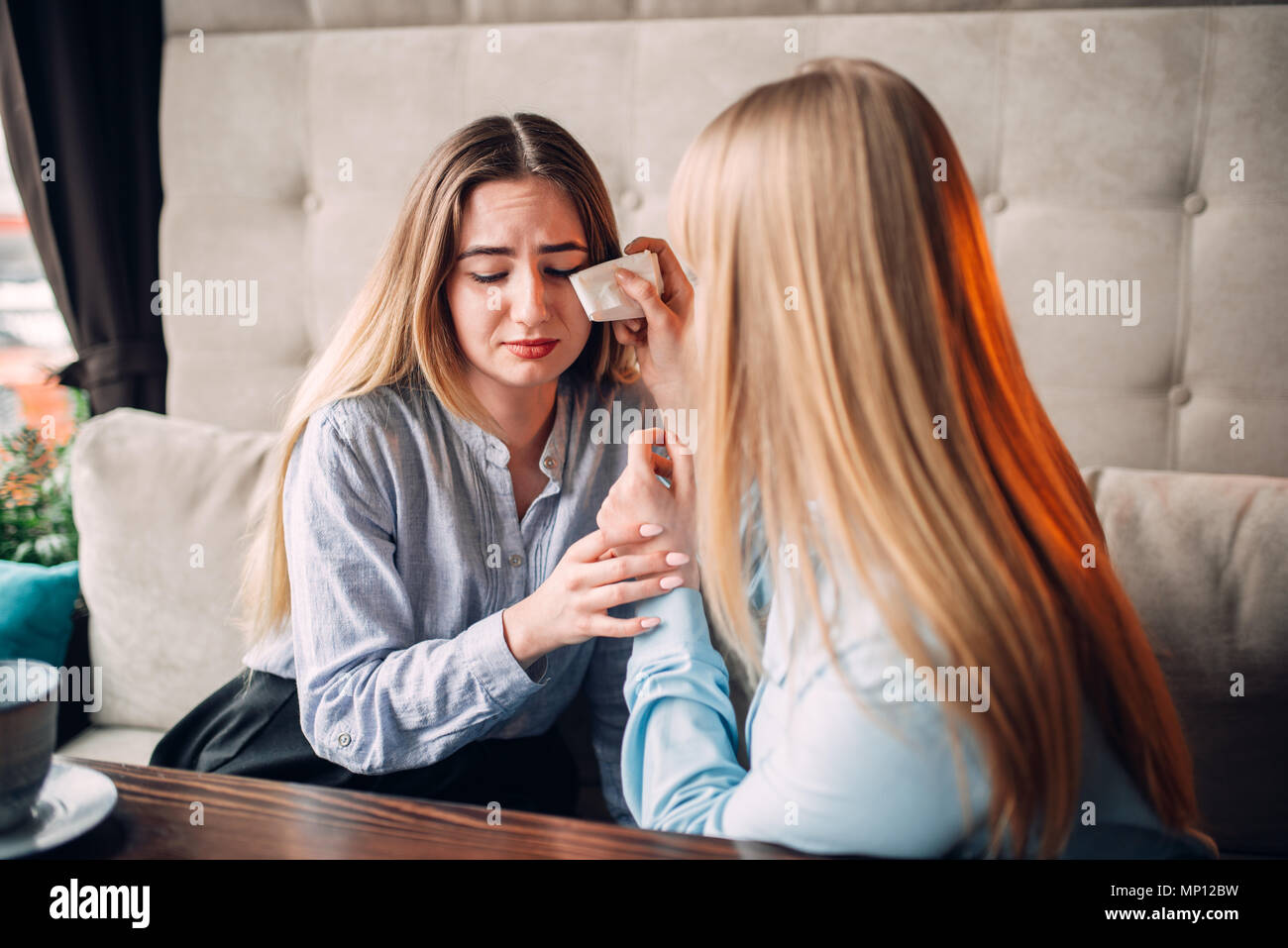 Young woman calms her girlfriend in cafe. Female friends leisures in restaurant, gossipers meeting - Stock Image