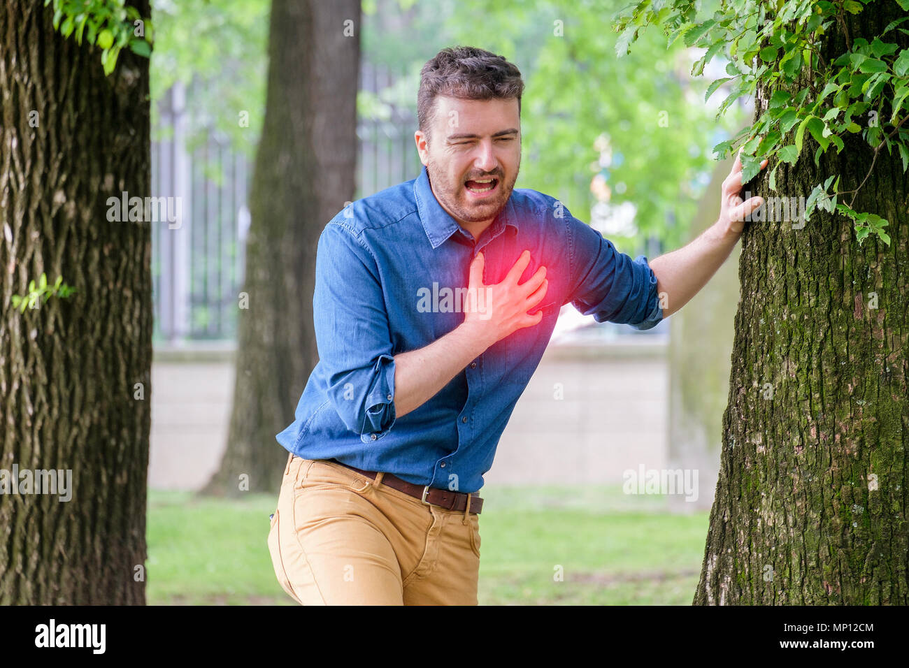 Severe heartache.Man pressing on chest with painful expression fist aid needed. - Stock Image