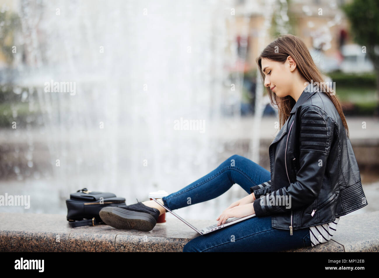 a beautiful teen woman is using her laptop computer outside, while sitting by a fountain in a town square - Stock Image