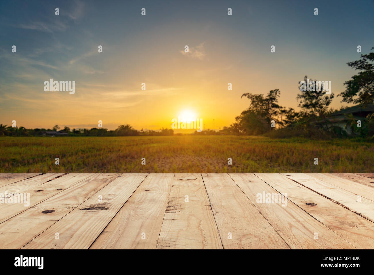 Empty wooden table top and display montage with blur background field sunset. - Stock Image