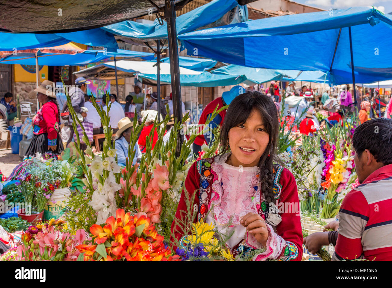 Pisac Peru Market, young Peruvian girl selling flowers at Pisac Market, Sacred Valley Peru, Cusco Region. Stock Photo