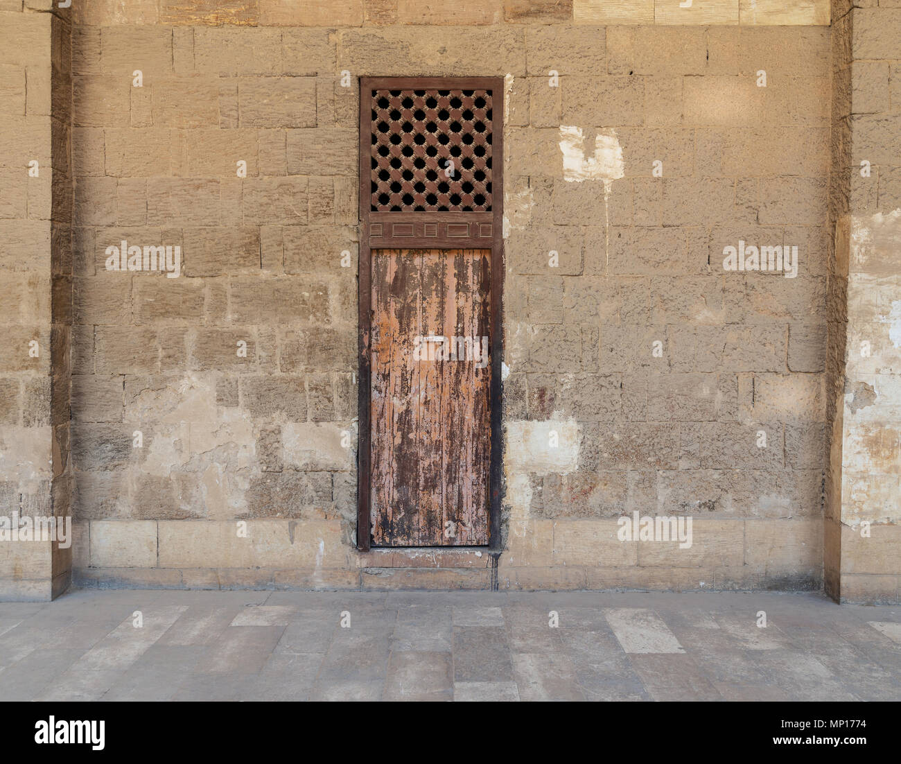 Facade of old abandoned stone bricks wall with one weathered wooden door and wooden grid window, Old Cairo, Egypt - Stock Image