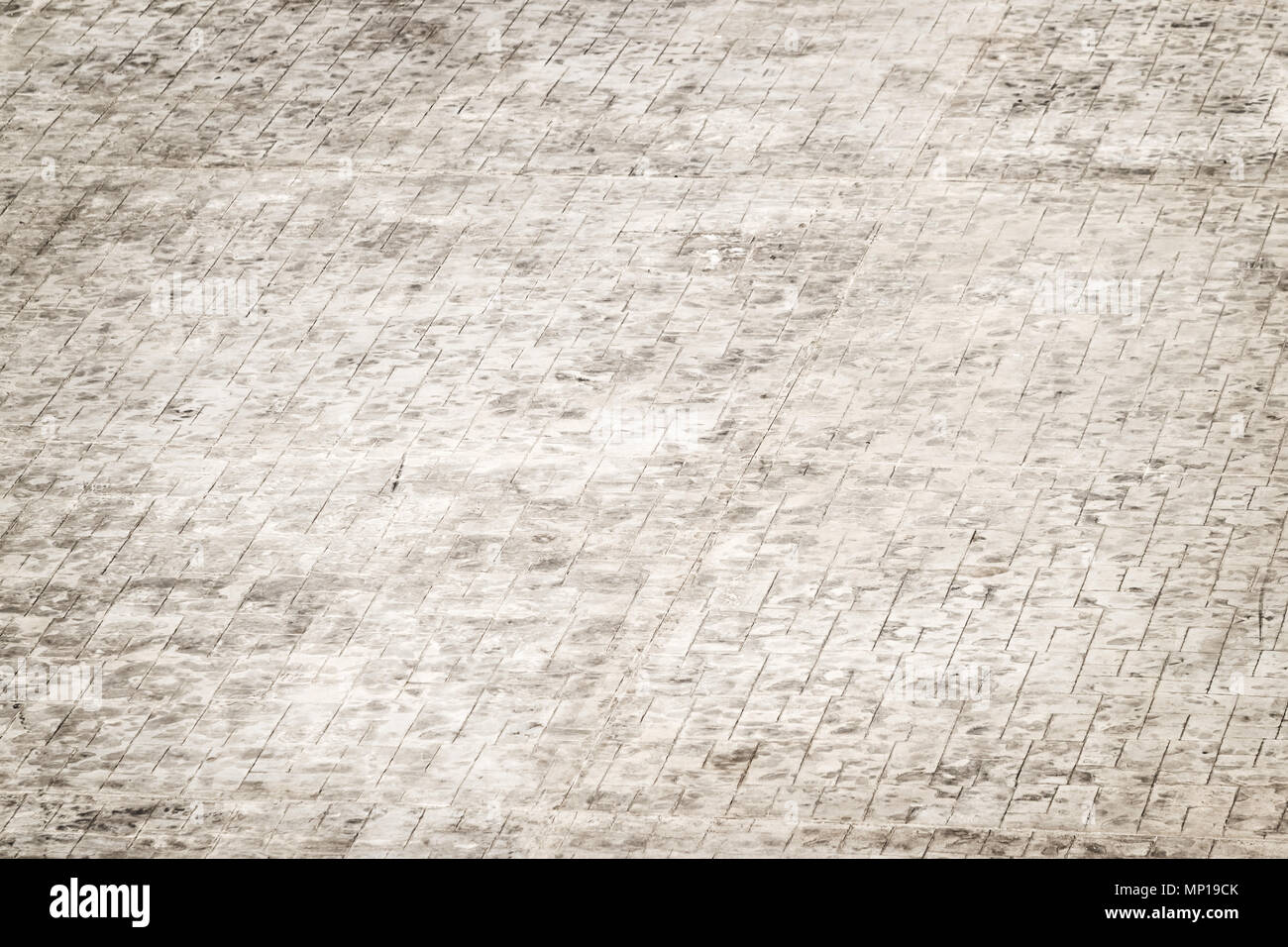 grey tiled floor of the parking place - Stock Image