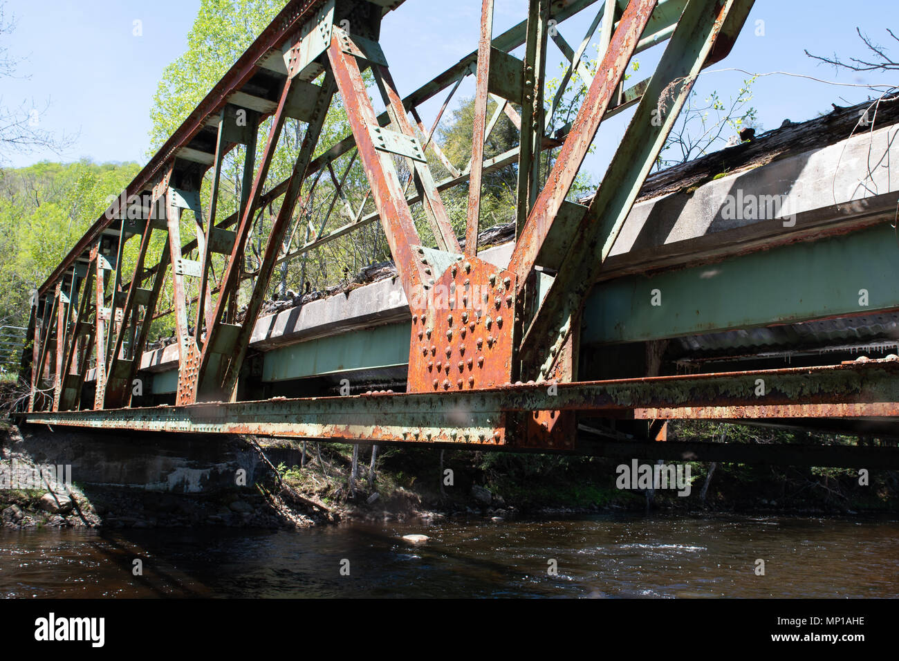 An old deteriorating closed bridge across the Sacandaga River in the Adirondack Mountains, NY, USA. - Stock Image
